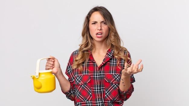 Dość szczupła kobieta wyglądająca na złą, zirytowaną i sfrustrowaną, trzymająca czajnik
