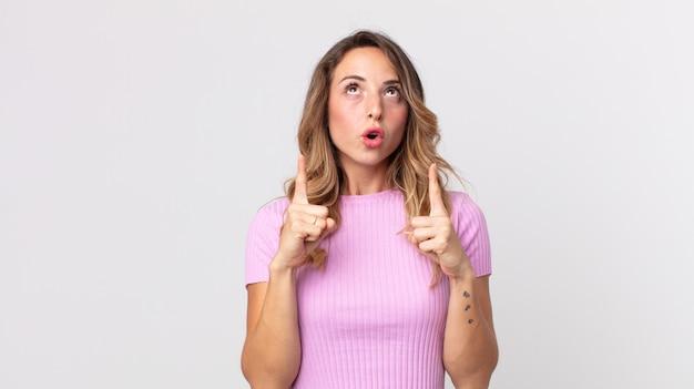 Dość szczupła kobieta wyglądająca na zszokowaną, zdumioną i z otwartymi ustami, wskazującą w górę obiema rękami, aby skopiować przestrzeń