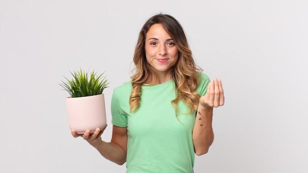 Dość szczupła kobieta wykonująca gest kaprysu lub pieniędzy, każąca ci zapłacić i trzymająca roślinę ozdobną