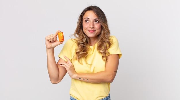 Dość szczupła kobieta wzrusza ramionami, czuje się zdezorientowana i niepewna, trzymając baterie