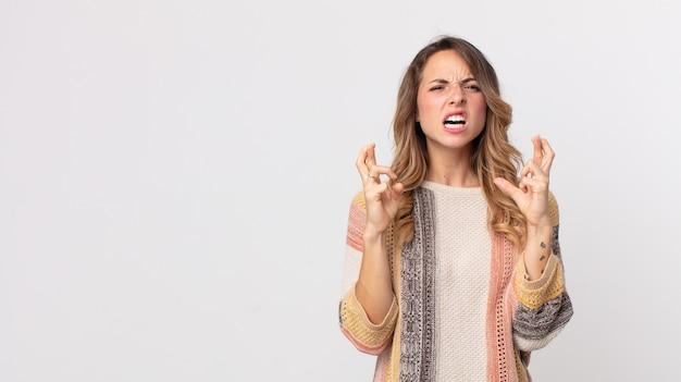 Dość szczupła kobieta z niepokojem krzyżuje palce i liczy na szczęście ze zmartwionym spojrzeniem