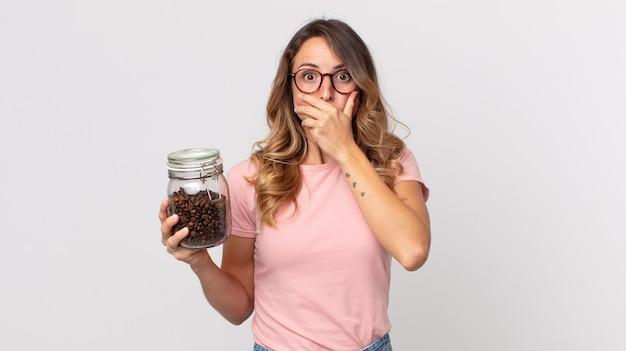 Dość szczupła kobieta zakrywająca usta rękami zszokowana i trzymająca butelkę ziaren kawy