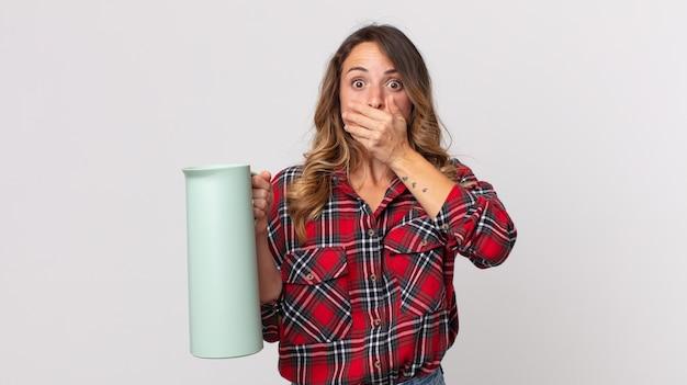 Dość szczupła kobieta zakrywająca usta rękami zszokowanym termosem z kawą