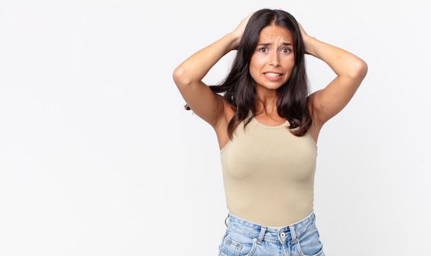 Dość szczupła latynoska kobieta czuje się zestresowana, niespokojna lub przestraszona, z rękami na głowie