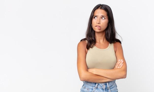 Dość szczupła latynoska kobieta wątpi lub myśli, przygryza wargę i czuje się niepewnie