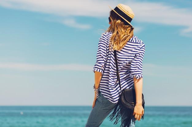 Dość szczupły blond stylowa kobieta w słomkowym kapeluszu i okularach przeciwsłonecznych pozuje na rajskiej tropikalnej plaży