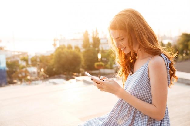 Dość uśmiechający się imbir kobieta w sukni za pomocą smartfona