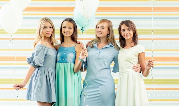 Dość uśmiechający się nastolatki w sukienkach stojących wraz z balonów na przyjęcie urodzinowe