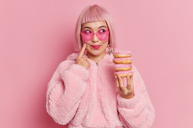 Dość uśmiechnięta azjatka słodycz z modnymi różowymi włosami nosi okulary przeciwsłoneczne i futro trzyma kupę pączków pozuje w domu marzenia o czymś. zdjęcia monochromatyczne. kobieta lubi jeść pączki