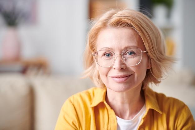 Dość uśmiechnięta dojrzała kobieta w okularach i casual, stojąca przed kamerą i patrząc na ciebie w środowisku domowym