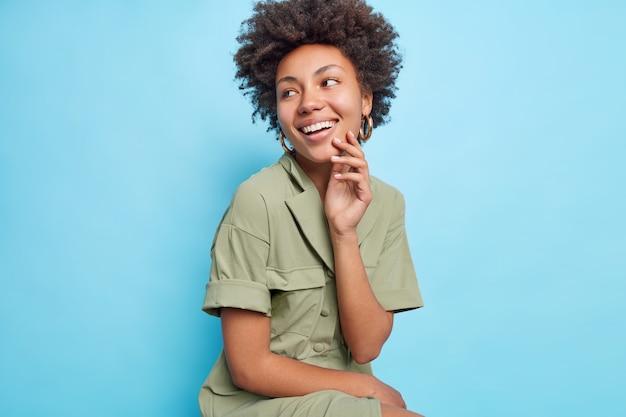 Dość uśmiechnięta kobieta z kręconymi włosami w stylu afro odwraca wzrok, szeroko uśmiecha się, pokazuje idealne białe zęby, ma na sobie stylową sukienkę skoncentrowaną po lewej stronie na białym tle nad niebieską ścianą