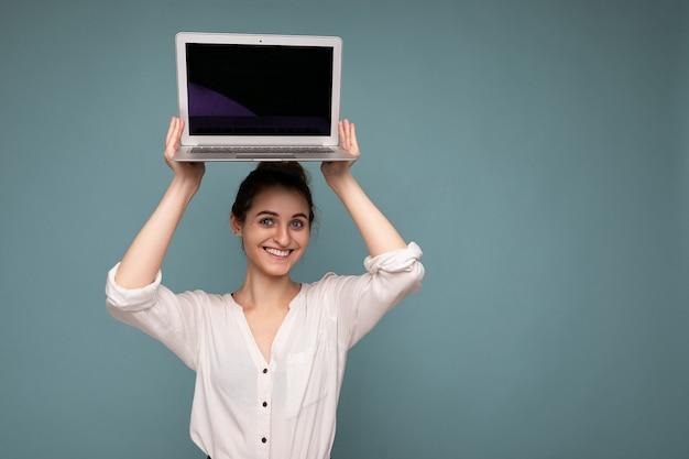 Dość uśmiechnięta młoda kobieta trzyma komputer netbook, patrząc na kamerę, ubrana w białą koszulę na białym tle na niebieskim tle