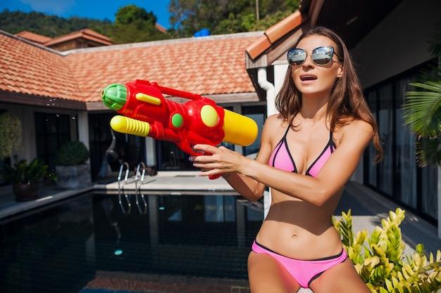 Dość uśmiechnięta szczęśliwa kobieta bawiąca się zabawką watergun przy basenie na letnich tropikalnych wakacjach w hotelu willowym, bawiąca się w kostiumie kąpielowym bikini, kolorowy styl, imprezowy nastrój