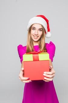 Dość uśmiechnięta szczęśliwa pani w krótkiej różowej sukience i noworocznym kapeluszu trzyma w rękach niespodziankę z papierowego pudełka