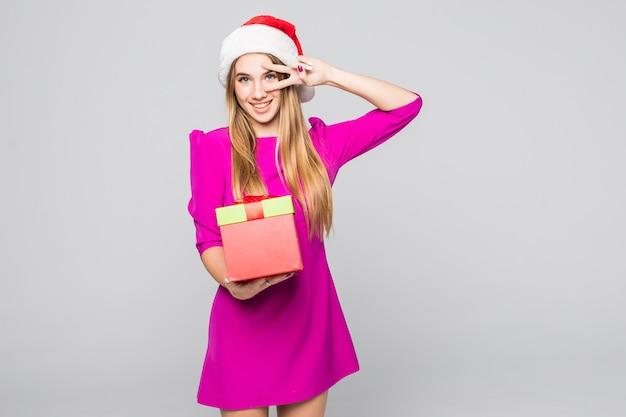 Dość uśmiechnięta zabawna szczęśliwa dziewczyna w krótkiej różowej sukience i noworocznym kapeluszu trzyma papierową niespodziankę w dłoniach