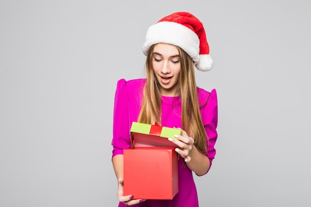 Dość uśmiechnięta zabawna szczęśliwa pani w krótkiej różowej sukience i noworocznym kapeluszu trzyma pudełko niespodziankę w dłoniach