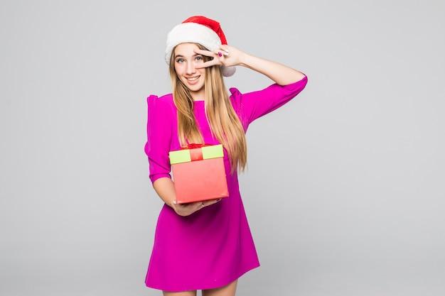 Dość uśmiechnięta zabawna szczęśliwa pani w krótkiej sukience i noworocznym kapeluszu trzyma papierową niespodziankę w dłoniach
