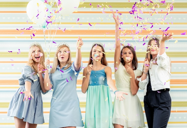 Dość uśmiechnięte nastolatki w sukienkach z radością podniosły razem ręce i biegają slaperów z błyskiem na przyjęciu urodzinowym
