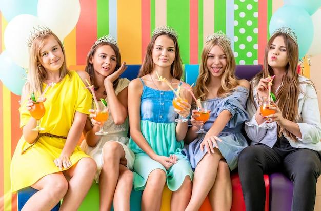 Dość uśmiechnięte nastoletnie dziewczyny w sukienkach i koronach siedzą tuląc się razem na kolorowej kanapie na przyjęciu urodzinowym