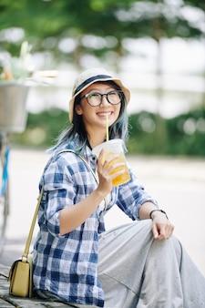 Dość wesoła młoda chinka w okularach odpoczywa na świeżym powietrzu i pije orzeźwiający koktajl