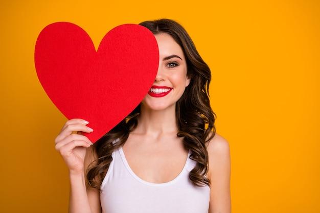 Dość wesoła pani trzyma dużą papierową pocztówkę w kształcie serca
