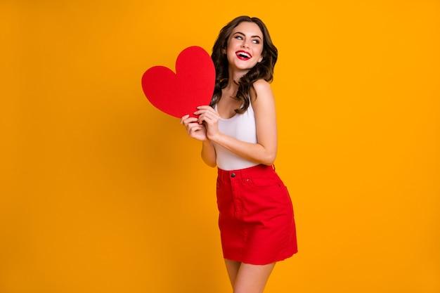 Dość wesoła pani wyglądająca z boku trzyma duże papierowe serce