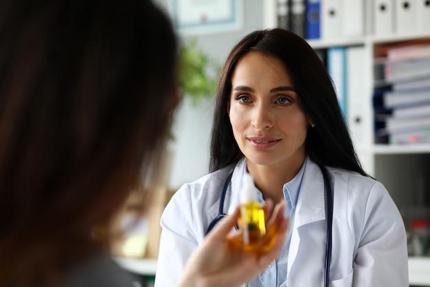 Dość wesoły żeński lekarz rodzinny, podający pacjentowi olej z marihuany