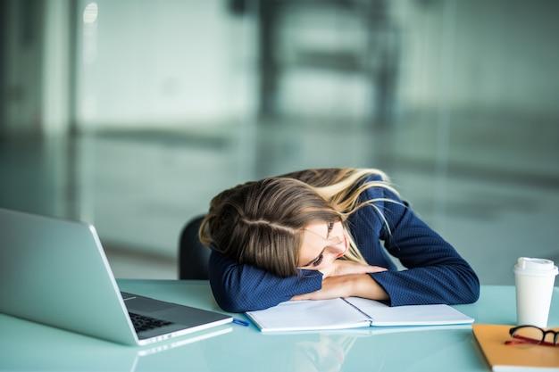 Dość wyczerpana młoda bizneswoman siedzi przy biurku do spania w swoim biurze