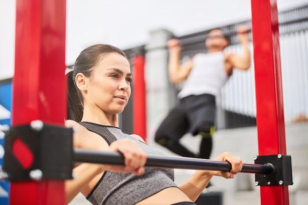 Dość wysportowana kobieta i silny mężczyzna ćwiczą i podciągają się na drążkach na świeżym powietrzu