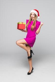 Dość zabawna szczęśliwa pani w krótkiej różowej sukience i noworocznym kapeluszu trzyma w rękach niespodziankę z papierowego pudełka
