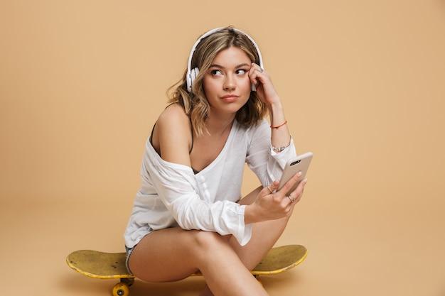 Dość zdenerwowana młoda dziewczyna w słuchawkach, siedząca na deskorolce na białym tle nad żółtą ścianą, trzymająca telefon komórkowy