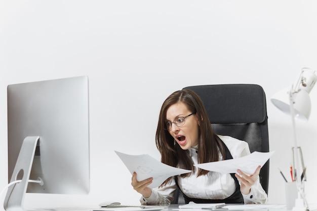 Dość zła biznesowa kobieta w garniturze siedzi przy biurku z dokumentami, pracuje przy komputerze z nowoczesnym monitorem w jasnym biurze, przeklina i krzyczy, rozwiązuje problemy,