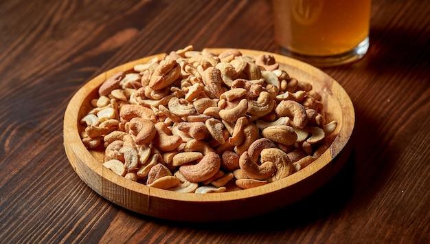 Doskonałą przekąską do piwa są słone orzechy nerkowca w drewnianym talerzu.