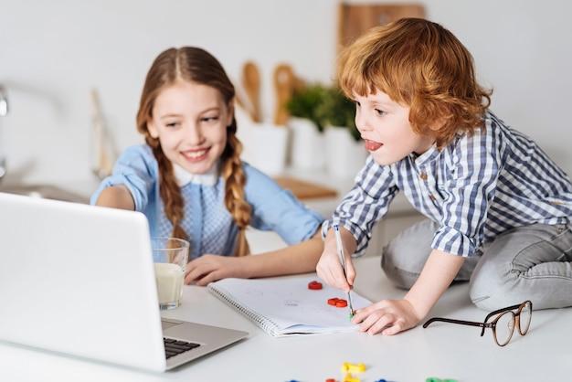 Doskonałe narzędzie. wspaniała, oszałamiająca młoda dama demonstruje coś na swoim laptopie swojemu bratu, a on zapisuje wszystko, siedząc na stole