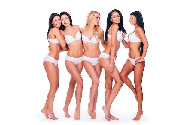 Doskonałe piękności. pełna długość pięciu pięknych kobiet w bieliźnie, które łączą się ze sobą i uśmiechają, stojąc razem na białym tle