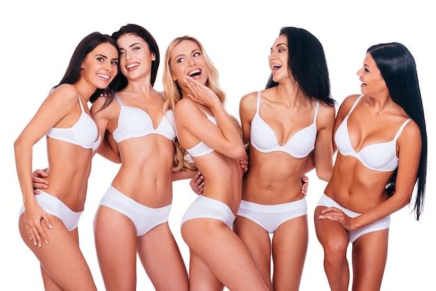 Doskonałe piękności. pięć pięknych kobiet w bieliźnie pozuje i wygląda naturalnie, stojąc razem na białym tle