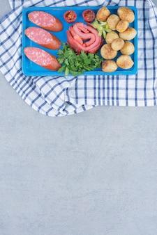 Doskonałe przekąski. ziemniak, boczek salami z warzywami.