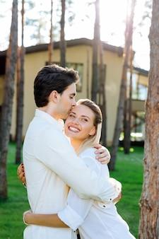 Doskonałe relacje. zachwycona piękna kobieta uśmiechnięta podczas pocałunku przez swojego chłopaka
