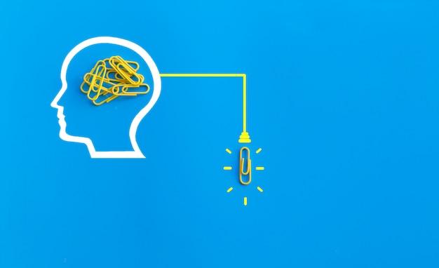 Doskonałego pomysłu pojęcie z ludzkim mózg, spinacz do papieru, główkowanie, twórczość, żarówka na błękitnym tle, nowy pomysłu pojęcie