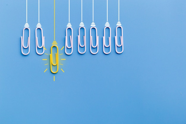 Doskonałego pomysłu pojęcie z spinaczem, główkowaniem, kreatywnością, żarówką na błękitnym tle, nowy pomysłu pojęcie.