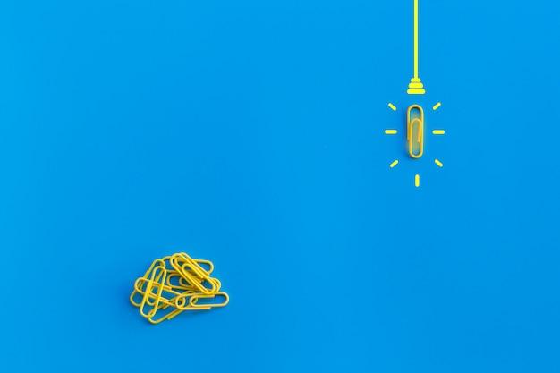 Doskonałego pomysłu pojęcie z spinaczem, główkowaniem, twórczością, żarówką na błękitnym tle, nowy pomysłu pojęcie.