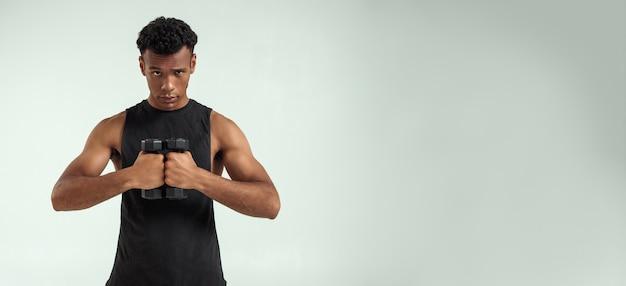 Doskonałość. muskularny młody człowiek afryki w sportowej, trzymając czarne hantle stojąc na szarym tle. baner internetowy. koncepcja sportowa