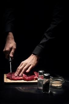Doskonały odbiór. zbliżenie na ręce młodych mans siekanie mięsa podczas gotowania i pracy jako szef kuchni w restauracji.