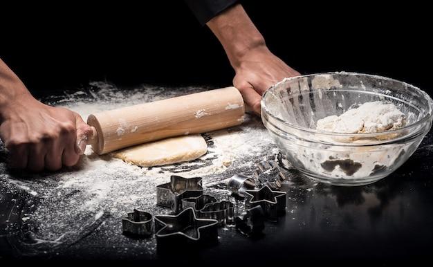Doskonały sprzęt. zbliżenie na ręce szefa kuchni mans wyrabiania ciasta i przy użyciu wałka do ciasta podczas gotowania w restauracji.