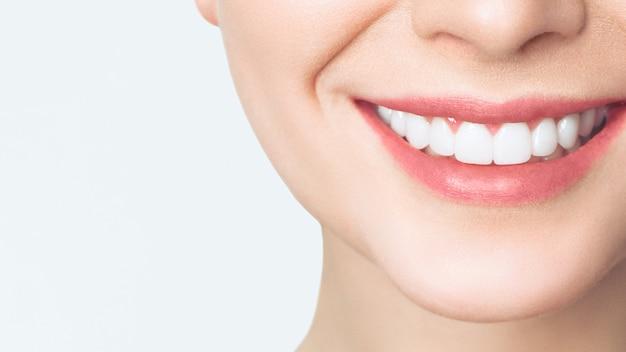 Doskonały uśmiech zdrowych zębów młodej kobiety.