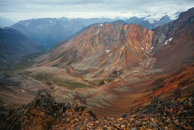 Doskonały widok z dużych spiczastych skał na pstrokatą dolinę górską. malowniczy krajobraz górski z wielokolorowymi spiczastymi skałami. kolorowa góralska sceneria z ostrymi skałami i wielokolorową górską doliną.