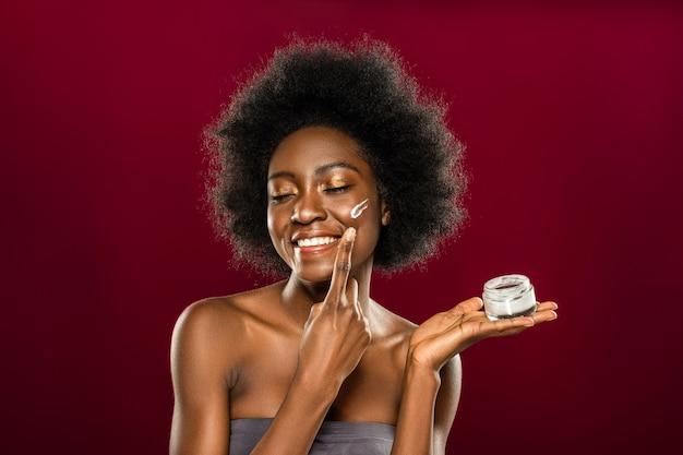 Doskonały wygląd. zachwycona afroamerykańska kobieta nakładająca krem dbająca o swój wygląd