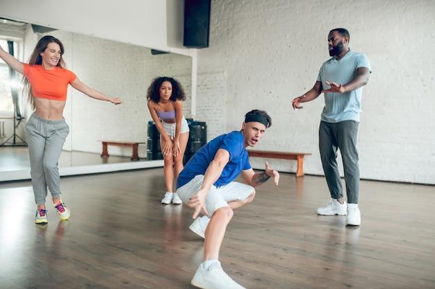 Doskonały wynik. młody sportowy emocjonalny facet w opasce tańczy w kucki wyciągając nogę w kręgu przyjaciół w sali tanecznej