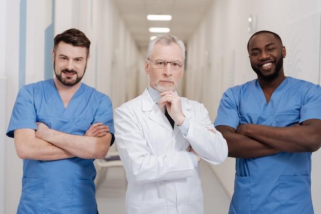 Doskonały zespół medyczny w historii. uśmiechnięci profesjonalni, wykwalifikowani lekarze pracujący w klinice, wykazujący się pewnością siebie i pozytywnym wyrażaniem