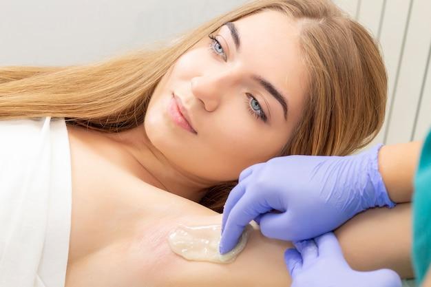 Dosładzanie: depilacja z płynnym cukrem pod pachą. mistrz cukrowania w wykonywaniu zabiegu depilacji dla kobiet. depilacja płynną pastą cukrową.